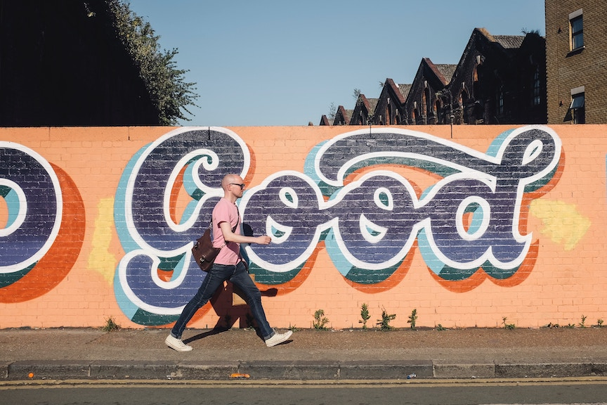 A man exercises by walking past a mural spelling out Good on a quiet street