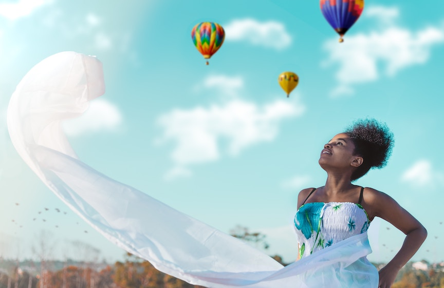 A woman in a white dress with a blue flower pattern looks up at hot air balloons in the sky