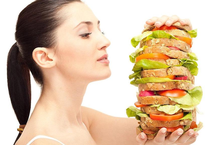 A woman looks longingly at a club sandwich made with twelve slices of oat bread and salad